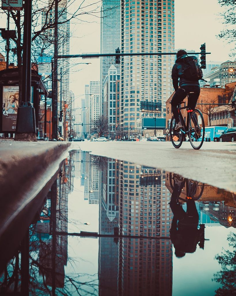 Ground-level view of a city street, with a large reflective puddle in the gutter and a person on a bicycle heading toward the large buildings of the downtown area.